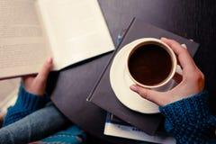 Una muchacha con café y un libro foto de archivo