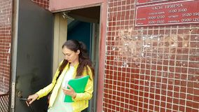 Una muchacha con una carpeta de documentos deja rápidamente la puerta de una institución almacen de metraje de vídeo