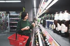 Una muchacha con una cesta roja elige el alcohol en un supermercado El hacer compras para la cerveza en la tienda imagen de archivo