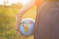 Una muchacha con el backback que sostiene el globo Imagenes de archivo
