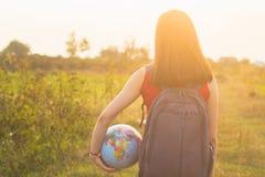 Una muchacha con el backback que sostiene el globo Foto de archivo libre de regalías