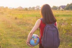 Una muchacha con el backback que sostiene el globo Fotos de archivo