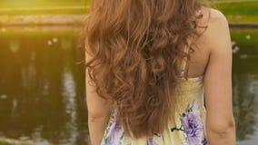 Una muchacha con el de largo, hermoso y rizado pelo contra el contexto de una charca en el parque Primer del pelo La muchacha sen imagen de archivo
