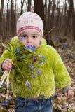 Una muchacha con el manojo de bluebells en bosque del resorte Imagen de archivo libre de regalías