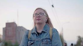 Una muchacha con el pelo blanco en vidrios y una chaqueta del dril de algodón da un paseo a través de la ciudad de igualación La  metrajes