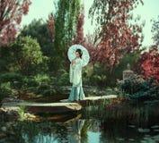 Una muchacha con el pelo largo, negro adornado con Kandzashi, las flores y los pernos largos con las gotas cristalinas Geisha en  Fotos de archivo