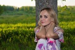Una muchacha con el pelo ondulado ligero se sienta por un árbol en el parque Fotografía de archivo libre de regalías