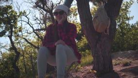 Una muchacha con el pelo oscuro en un negro y una camisa roja, pañuelo y los vidrios se sienta en el bosque, mirando alrededor almacen de video