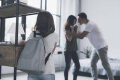 Una muchacha con el pelo oscuro y una mochila detrás de ella retrocede cerca de los estantes y mira a sus padres regañar Foto de archivo libre de regalías