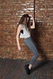 Una muchacha con el pelo rizado baila en un sótano del almacén del ladrillo Imagenes de archivo