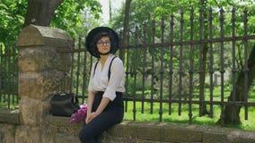 Una muchacha con el sombrero en su cabeza y en vidrios se sienta en la cerca de piedra almacen de video