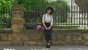 Una muchacha con el sombrero en su cabeza y en vidrios se sienta en la cerca de piedra metrajes