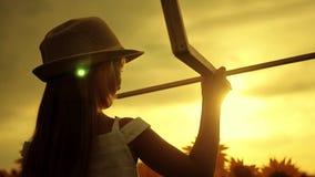 Una muchacha con el sombrero que juega con un aeroplano de madera Niño feliz que juega con el aeroplano del juguete en campo del