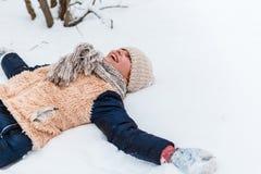 Una muchacha con el trineo Adolescente hermoso que tiene exterior de la diversión en una madera con nieve en invierno concepto ac fotografía de archivo