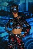 Una muchacha con una figura delgada en un traje fantástico del espejo con una máscara de los espejos que se realizan en la arena fotografía de archivo libre de regalías