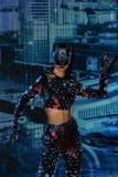 Una muchacha con una figura delgada en un traje fantástico del espejo con una máscara de los espejos que se realizan en la arena imágenes de archivo libres de regalías