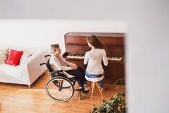 Una muchacha con la abuela en la silla de ruedas que juega el piano Foto de archivo libre de regalías