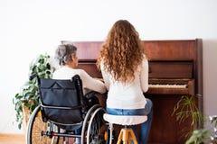 Una muchacha con la abuela en la silla de ruedas que juega el piano Fotos de archivo libres de regalías