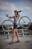 Una muchacha con la bici cielo-azul Fotografía de archivo libre de regalías