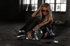 Una muchacha con la bola de discoteca en la casa abandonada Foto de archivo libre de regalías