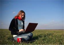 Una muchacha con la computadora portátil Foto de archivo