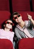 Una muchacha con la madre en el cine 3D Imagen de archivo libre de regalías