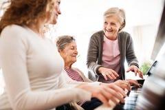 Una muchacha con la madre y la abuela que juegan el piano Fotografía de archivo