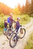 Una muchacha con la madre y el hermano que disfrutan del ciclo Fotografía de archivo