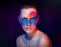 Una muchacha con la pintura inusual de la carrocería del maquillaje brillante Imagen de archivo libre de regalías