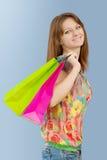 Una muchacha con las bolsas de papel que miran la cámara y la sonrisa Fotos de archivo libres de regalías