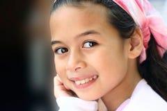 Una muchacha con los ojos marrones y el pañuelo rosado Fotos de archivo