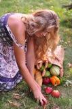 Una muchacha con los productos alimenticios en la hierba Imagenes de archivo