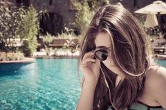 Una muchacha con música que escucha de las gafas de sol y de los auriculares Foto de archivo