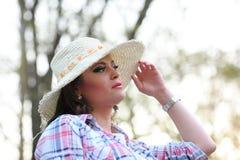 Una muchacha con una mirada pensativa y un sombrero en sus actitudes principales en un parque fotos de archivo libres de regalías