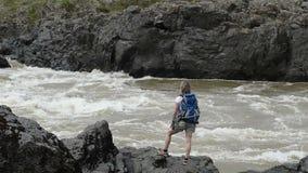 Una muchacha con una mochila se está colocando en el banco de un río de la montaña almacen de video