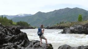 Una muchacha con una mochila se está colocando en el banco de un río de la montaña almacen de metraje de vídeo