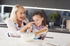 Una muchacha con su abuela cocina una torta hecha en casa Engañan alrededor y ríen Imágenes de archivo libres de regalías