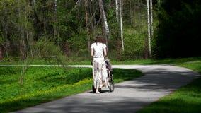 Una muchacha con un cochecito camina a lo largo de la trayectoria del parque a lo largo de los árboles y de los céspedes verdes metrajes