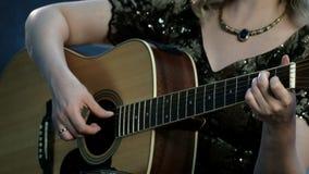 Una muchacha con un collar en su cuello toca una guitarra acústica La mano derecha toca las secuencias, los controles de la mano  almacen de video