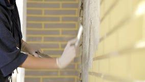 Una muchacha con un cuchillo de masilla, goma spackling Un método de aplicar una capa de una espátula y de trabajo con goma de la metrajes
