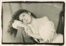 Una muchacha con un hombro desnudo en la silla imagen de archivo libre de regalías