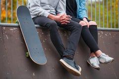 Una muchacha con un individuo que se sienta en el punto fijo al lado de un monopatín en un parque del patín Imagen de archivo libre de regalías