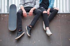 Una muchacha con un individuo se está sentando en el punto fijo al lado de un monopatín en un parque del patín Front View Fotografía de archivo libre de regalías