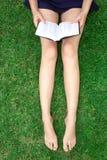 Una muchacha con un libro se está sentando en la hierba Piernas femeninas delgadas largas hermosas imágenes de archivo libres de regalías