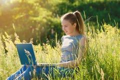 Una muchacha con un ordenador portátil en naturaleza entre la hierba verde foto de archivo
