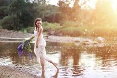 Una muchacha con un ramo de lupines púrpuras foto de archivo libre de regalías