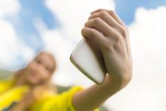 Una muchacha con un teléfono en su mano al aire libre Foto de archivo