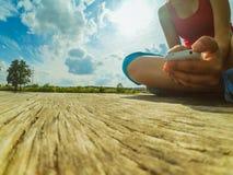 Una muchacha con un teléfono en su mano se sienta en la superficie de madera Imagen de archivo libre de regalías