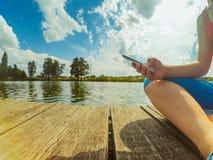 Una muchacha con un teléfono en su mano se sienta en la superficie de madera Fotografía de archivo libre de regalías