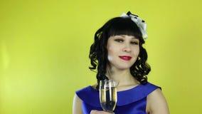 Una muchacha con un vidrio de champán sonríe delante de la cámara almacen de metraje de vídeo